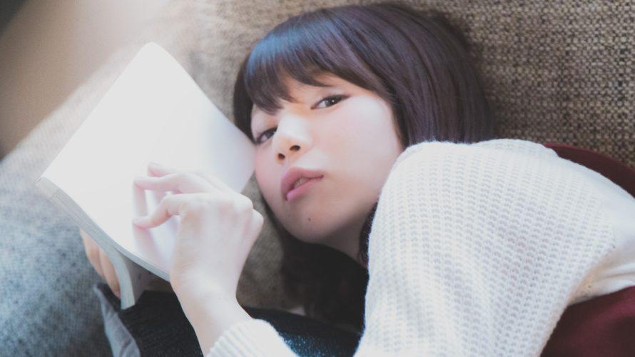 ソファーに寝転がりマンガを読む美女 [モデル:みき。]